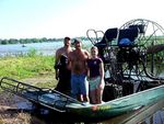 Volunteers pose with airboat used for trash collection.