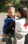Red Cross volunteer helps child during recent natural disaster.