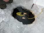 The VideoRay underwater robot enters through a hole in the ice.