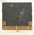 """This small block of AABC took direct, concentrated fire in its center from the 35 (now spent) .50 cal. BMG shells shown, on top of previous test fire. The projectiles in this test were easily contained, stopped safely at a depth of about 6"""" in the material. This block would easily absorb thousands of additional .50 cal. BMG rounds, fully protecting the persons and facilities behind. In front, for comparison, is a .50 cal. BMG next to a .30/06 cartridge, which is dwarfed."""