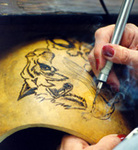 "A student creates a striking image in the ""Woodburning with Gourds"" class."