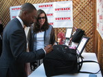 Eddie Murphy autographing the Vera Bradley Traveler Bag that will be auctioned on eBay next week.