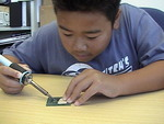 10 Year old hand soldering a small IC