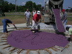 Workers spread specially-dyed concrete provided by The QUIKRETE® Companies into the purple heart mold.