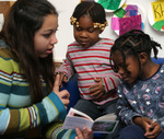 A student from Conrad Ball Middle school reads to two children from Denver Great Kids Head Start.