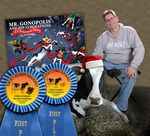 Uncle Hyggly with book, awards and Mr. Gonopolis' lead cow Bessie.