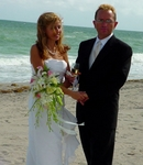 The bride and groom pose on the beach.