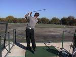 Chris Otis takes a swing at the golf driving range.