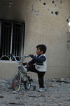 A child plays in the yard of his destroyed home where his four year old brother was killed by American fire.