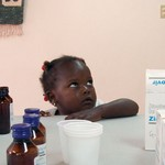 A young girl watches on in anticipation as she awaits her newly flavored medication.