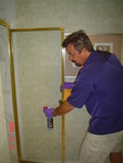 James Aiken, CEO of Tekon Universal Sciences Inc. applies a Tekon treatment to a shower door. Shower doors sealed and protected with Tekon's protective treatment protects the door from water corrosion and stains, and seals the surface to protect it from bacteria, viruses, mold and other toxins.