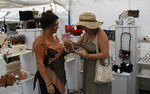 Designer Dede Atkins watches a customer expressing her delight at the Delray Affair in South Florida on April 21, 2006.