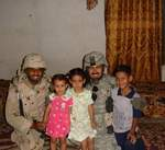 Captain James Van Thach and Major Alvaro Roa greeting Iraqi children