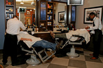 Barbers at work while clients relax