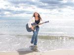 Pop Sensation Seven Silvasy on beach with Guitar.