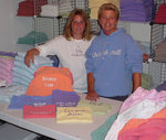 Kristine Fichera and Alyson Bruu pose in front of Lifestyle Tees from Liv'n Out Loud! Clothing line