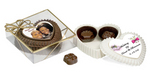 A chocolate heart shaped box with removable top filled with 3 truffles