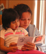 A mom and her child from the Enemy Swim FACE program take time to read one of their RealeBooks.