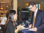 Participant receives Spotme device at World Economic Forum on East Asia 2007