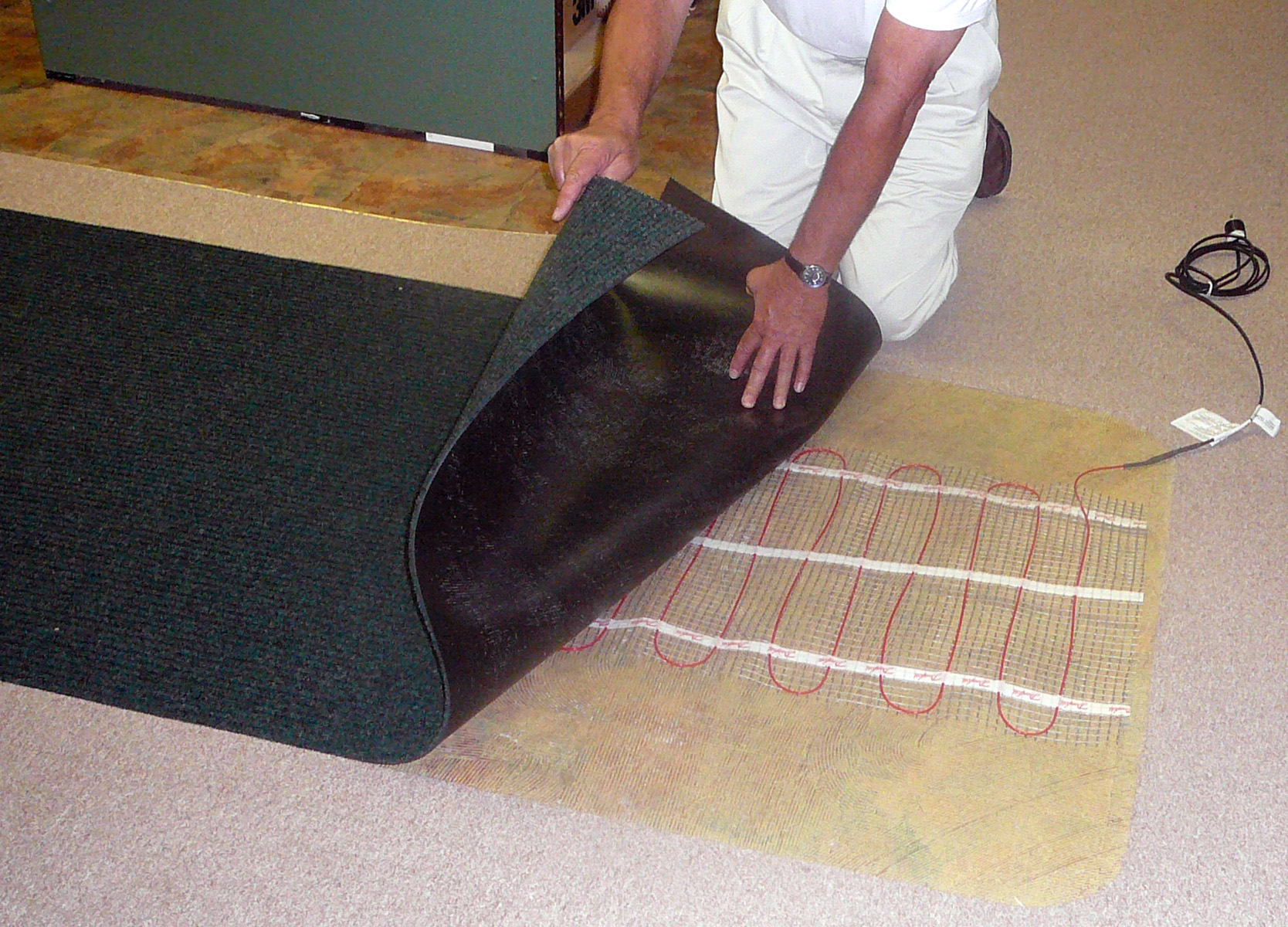 Under carpet or rug heated floor systems warm and dry wet floors martinson nicholls heated floor system being installed under carpetmartinson nicholls new speed heat and electric danfoss heating systems are designed to go dailygadgetfo Images