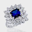 Princess-cut simulated sapphire engagement ring surrounded by double row of round cubic zirconia stones.