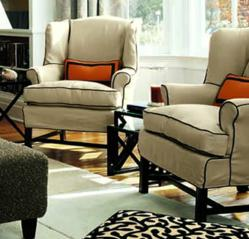 Two slipcovered wing chairs in living room setting.