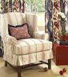 A casual heavy cotton stripe makes a comfy custom slipcover for this wing chair in a setting by Calico Corners - Calico Home.  Slipcovers can be made to fit tight as a glove, relaxed as shown here, or