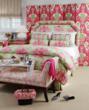 Honeysuckle pinks star with key lime greens in this colorful bedroom designed by Calico Corners - Calico Home.  Featured fabrics include the distinctive Shanghai Toile in Bermuda on the bed and the ik