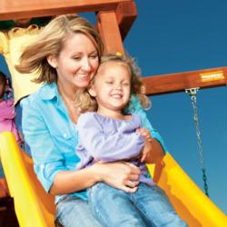 Mother and daughter are spending quality time playing on a Woodplay swing set!