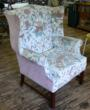A classic wing chair is dated by its Jacobean floral and rose velvet fabric covering.