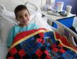 A happy recipient of a hand-crafted quilt delivered by a Quilts for Kids volunteer.