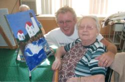 Proud patient and her son share joy over a new painting.