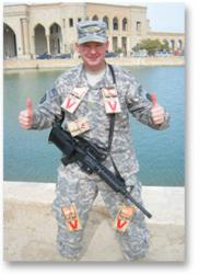 U.S. soldier stands with Victor Rodent Control trap donations.