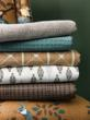 New DwellStudio fabrics stacked on a chair