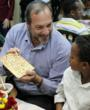 Rabbi Yechiel Eckstein, president of the International Fellowship of Christians and Jews, explains the significance of eating matzah to an Ethiopian child enjoying his first Seder.
