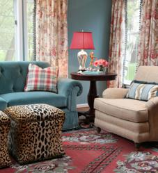 Blue tufted sofa and leopard-printed cotton velvet ottomans.