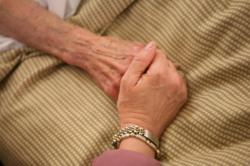 Home Instead Senior Care owner holds the hand of an elderly woman.