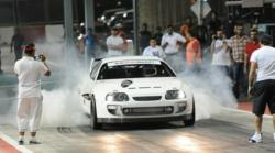 Ebrahim Kanoo of EKKAnoo Racing does a burnout in his Supra drag race car at the Bahrain International Circuit before a 7.76 elapsed time run