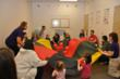 Judy Jones, far left, Owner and Director of Milestones in Music works with her students to bounce balls on a parachute to music. The children exercise inhibitory control and tempo variation by following the music as they move the parachute and balls to th