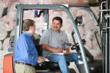 Marketplace Chaplains employee Paul Shirley talks with a Rasa Floors employee on his forklift during a regular Marketplace Chaplains visit.