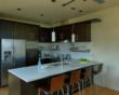 Custom kitchen layout features stainless steel shelving & architectural lighting