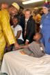 Sierra Leone Vice President Samuel Sam-Sumana shakes the hand of a pediatric patient in the hospital ward.