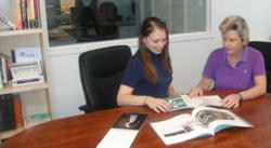Customer service representative Robin Clark reviews a printing manual with digital specialist Jessica Keniston in Braintree Printing's technical library.
