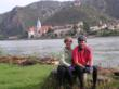 A couple relaxes along the Danube Bike Path with a medieval village in the background topped by an ancient castle ruin.