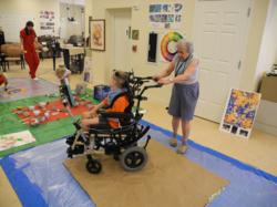 retirement community residents and child with disability engage in intergenerational art project