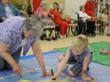 children and retirement community residents enjoy artwork together
