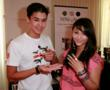 BooBoo Stewart holding a red level necklace. His sister Fivel is wearing a heart-shaped padlock ring.