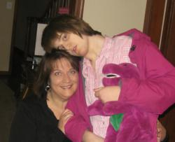 Daughter with autism in Barney costume standing next to seated mother.