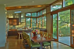 Kitchen and dining along great room window wall Portland prefab home by Stillwater Dwellings