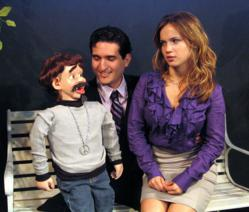 Scene from the new musical comedy, The Capitalist Ventriloquist, showing the heir to a hedge fund, Alan, who would rather be a singing ventriloquist, with ambitious dummy, Randy, and his fiance', Branda, who isn't sure she wants to be married to a ventril